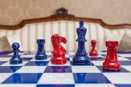 Navy blue and red Earl chessmen on a blue board