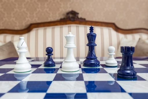 Navy Blue and White Earl chessmen on a blue board